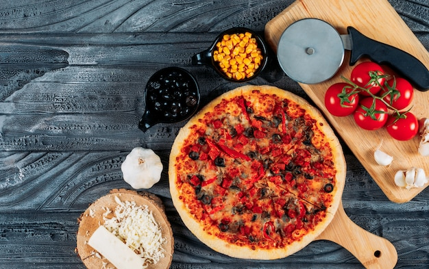 Set of a slice of cheese, garlic, tomatoes, olives, corn and a pizza cutter and pizza in a pizza board on a dark wooden background. top view.