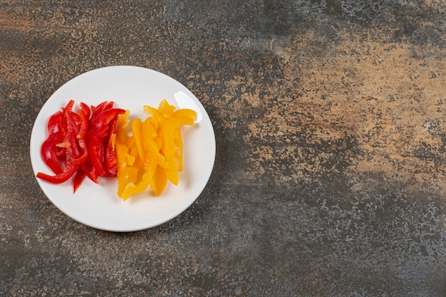 Set of sliced red and yellow peppers on white plate.