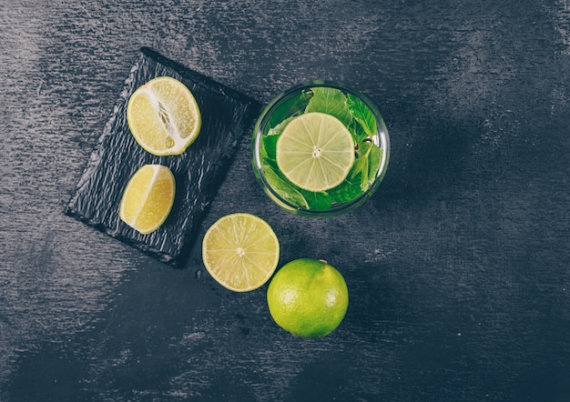 Set of slices and green lemons in a water glass on a black textured background. top view.
