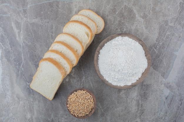 Set di fette di pane tostato con chicchi di avena sulla superficie in marmo