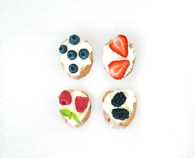 Set of small sweet sandwiches with cream-cheese and fresh forest berries