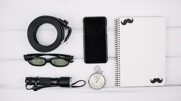 Set of smartphone near notebook and male accessories