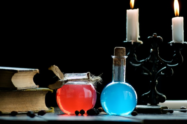 Set of sorcery book, magic potions and candles on table