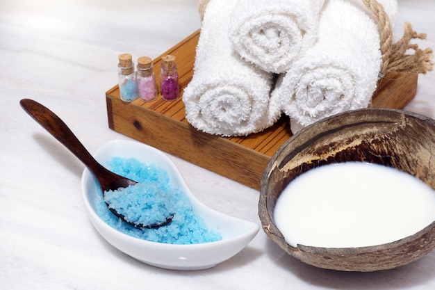 Set for spa procedures from coconut oil, soft towels, and blue bath salt on a white marble table.