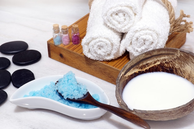Set for spa procedures from coconut oil, soft towels, hot stones and blue bath salt on a white marble table.