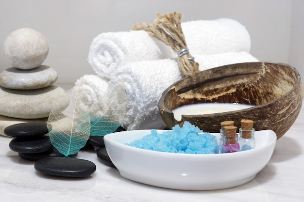 A set for spa treatments with coconut milk, hot stones and blue bath salt is located on a white marble countertop.