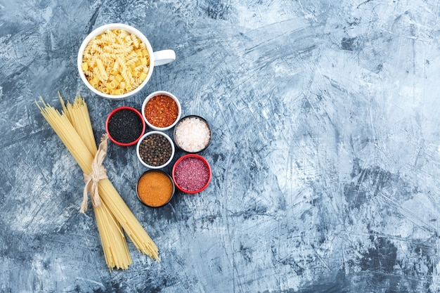 Set of spices and assorted pasta in a bowl on a grey plaster background. top view.