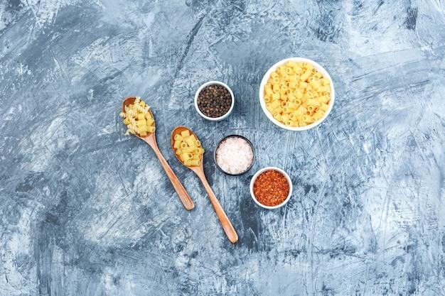 Set di spezie e pasta assortita in una ciotola e cucchiai di legno su uno sfondo di gesso grungy. laici piatta.