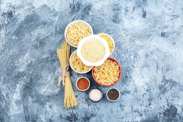 Set di spezie e pasta assortita in ciotole su uno sfondo di gesso grigio. vista dall'alto.