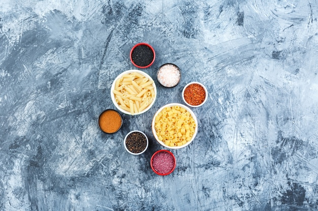 Set of spices and assorted pasta in bowls on a grey plaster background. top view.