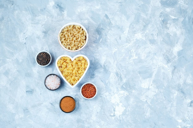 Set of spices and assorted pasta in bowls on a grungy grey background. top view.