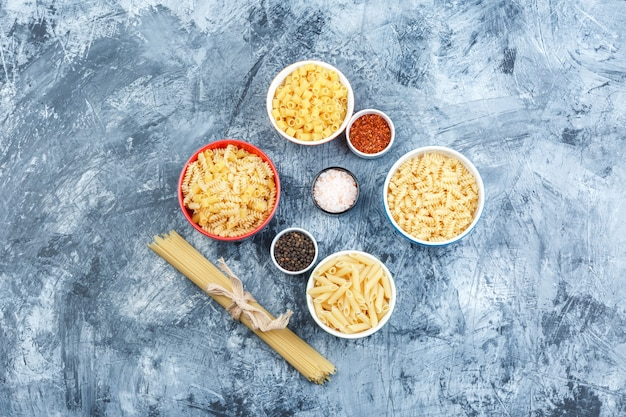 Set di spezie e pasta assortita in ciotole su uno sfondo di gesso grungy. laici piatta.