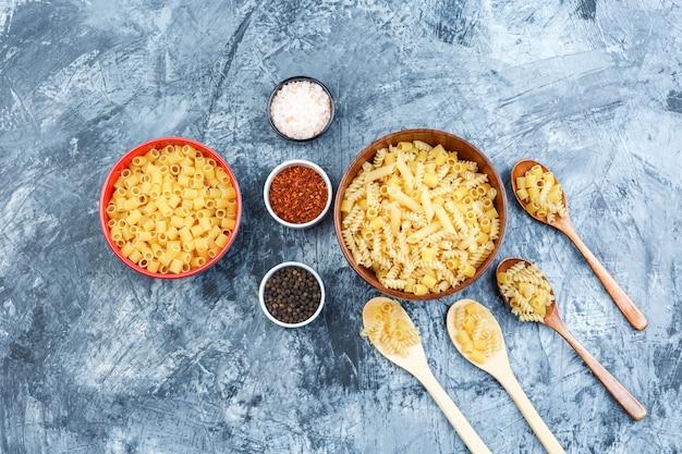 Set di spezie e pasta assortita in ciotole e cucchiai di legno su uno sfondo di gesso grungy. laici piatta.