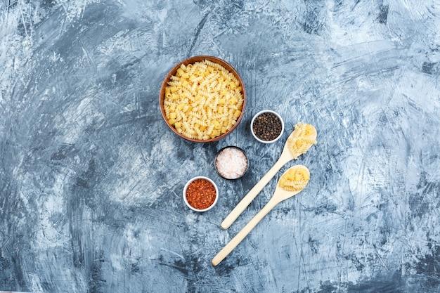 Set di spezie e pasta assortita in ciotola di argilla e cucchiai di legno su uno sfondo di gesso grungy. laici piatta.