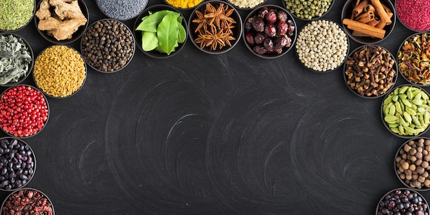 Set of spices on  black table with empty space for text.