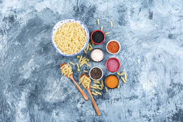 Set of spices and fusilli pasta in bowl and wooden spoons on a grey plaster background. top view.