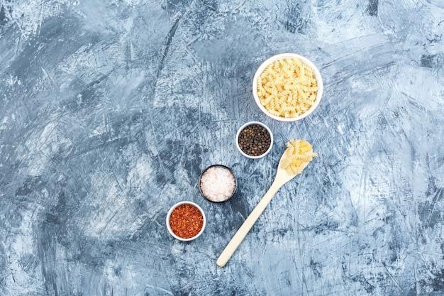 Set di spezie e fusilli in ciotola bianca e cucchiaio di legno su uno sfondo di gesso grungy. laici piatta.