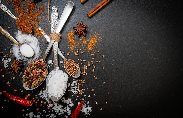 A set of spices and herbs with spoon and copy space on black background