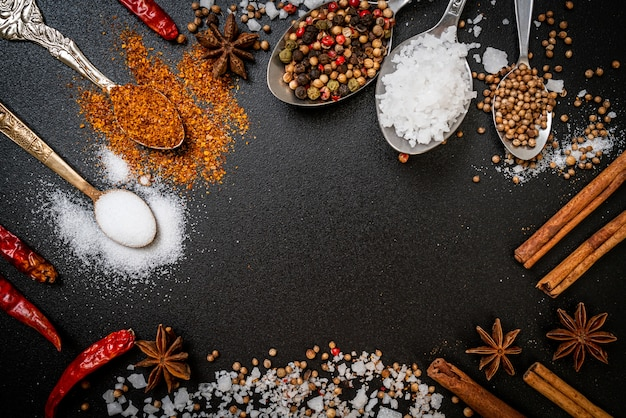 A set of spices and herbs with spoon and copy space on black