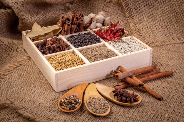 Set of spices (pepper, white pepper, black pepper, anise, caraway,) in a wooden box.