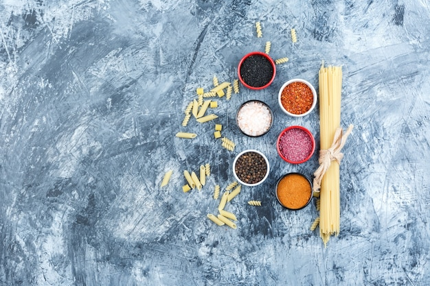 Set of spices and raw pasta on a grey plaster background. top view.