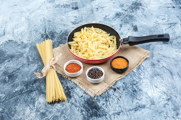Set of spices and raw pasta in a pan on plaster and piece of sack background. high angle view.