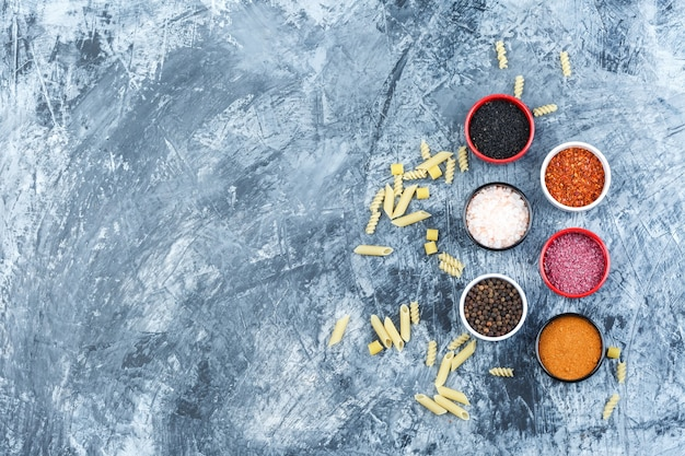 Set of spices and scattered pasta on a grey plaster background. top view.