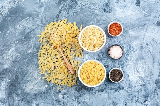 Set di spezie e pasta sparsa in cucchiaio di legno e ciotole su priorità bassa grungy dell'intonaco. laici piatta.