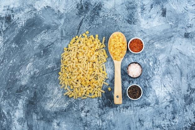 Set di spezie e pasta sparsa in un cucchiaio di legno su uno sfondo di gesso grungy. laici piatta.