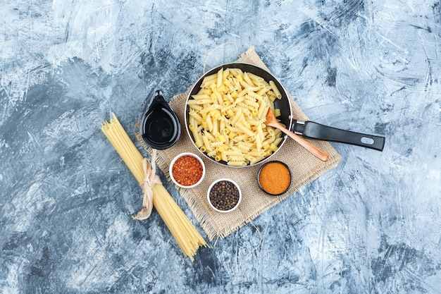 Set of spices, scoop, wooden spoon and raw pasta in a pan on plaster
