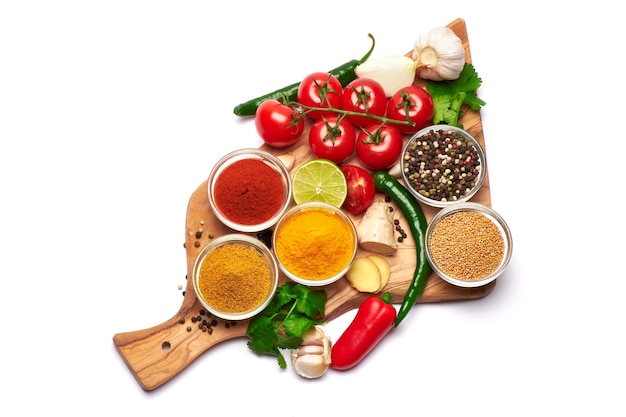 Set of spices and vegetables on wooden serving board