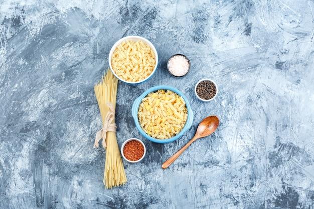Set di spezie, cucchiaio di legno e pasta assortita in ciotole su uno sfondo di gesso grigio. vista dall'alto.