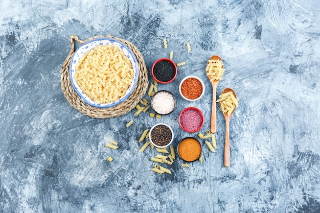 Set of spices, wooden spoons and fusilli pasta in a bowl on grey plaster and wicker placemat background. top view.