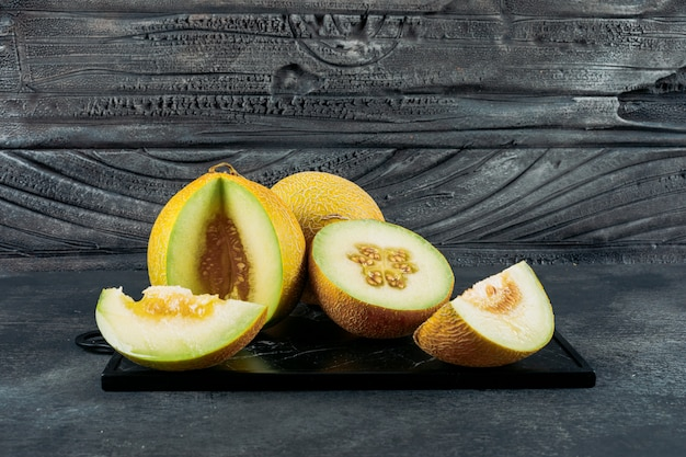 Set of split in half melon and sliced melons on a dark wooden background. side view.