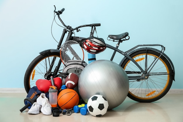 Set of sport equipment with bicycle near color wall