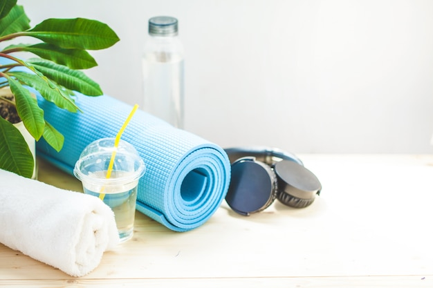 Set for sports. blue yoga mat towel headphones and a bottle of water on a light