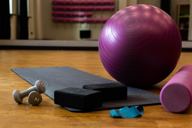 Set of sports equipment with fitness ball and yoga mat in the gym on the floor