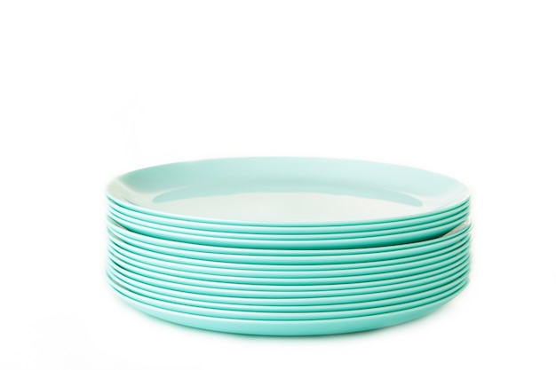 Set of stacked mint ceramic plates isolated on white. top view
