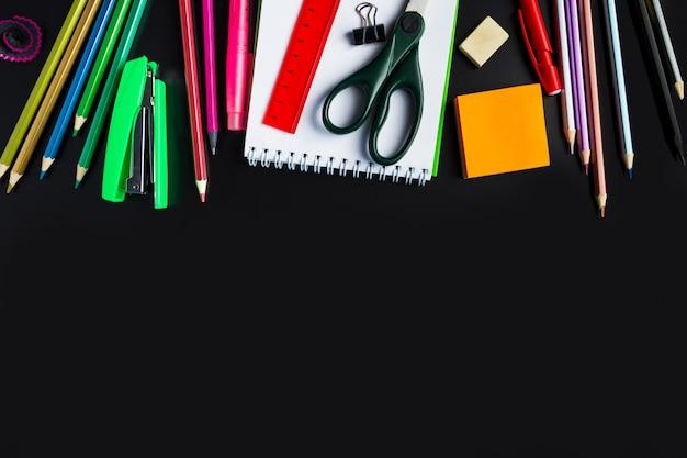Set of stationery on black background.