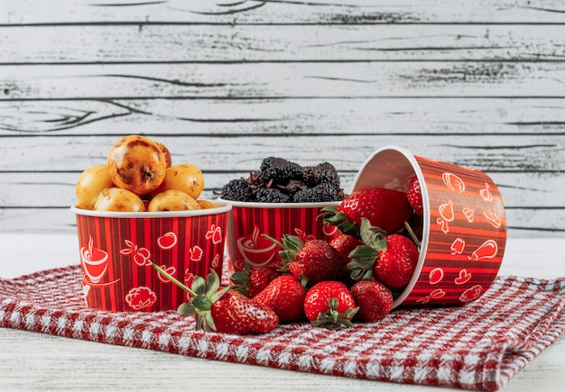 Set of strawberries, loquats and mulberries in a bowls on a cloth and light wooden background. side view.
