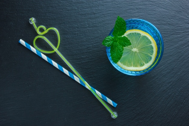 Set of straws and lemon slice in a blue bowl on a dark stone surface. top view.