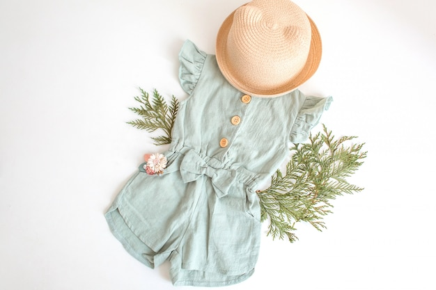 Set of summer children clothes for girl, stylish romper suit, straw hat and flower accessory.