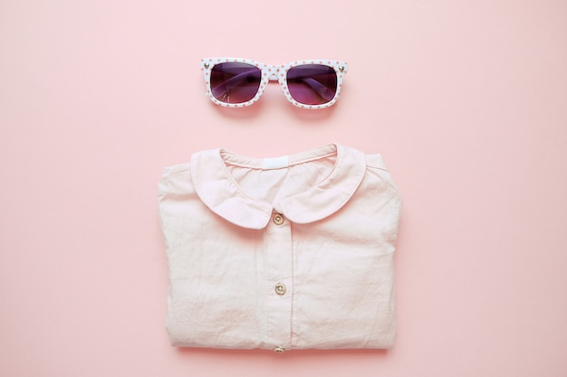 Set of summer childrens clothing on pink background. baby girl fashion look with shirt and glasses