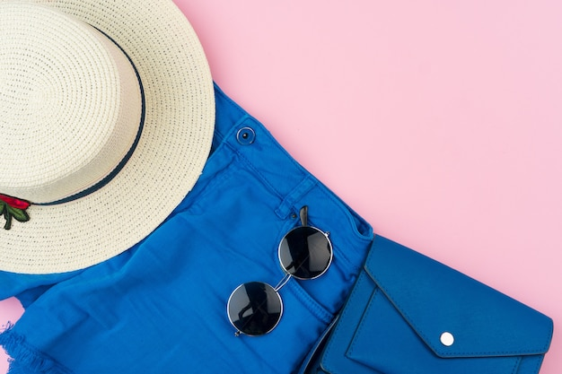Set of summer clothes for woman on pink surface