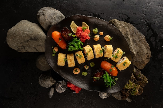 A set of sushi on a beautiful black plate. japanese dish. sushi rolls with japanese tamago amlet and salmon sashimi with rice, gunkans with red caviar, ginger.