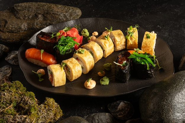 A set of sushi on a beautiful black plate. japanese dish. sushi rolls with japanese tamago omelet and salmon sashimi with rice.