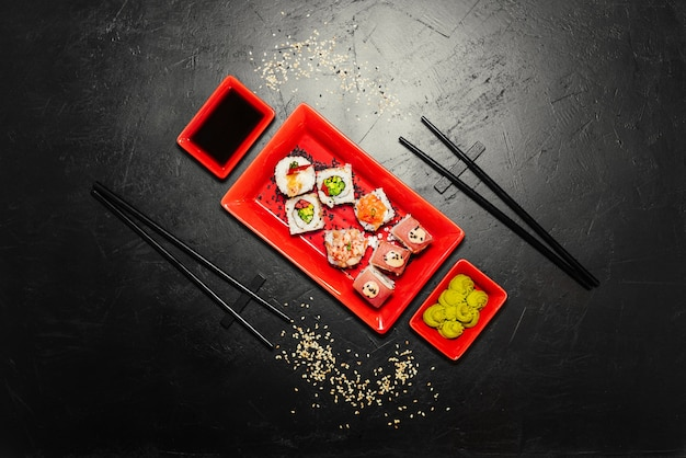Set of sushi, japanese knife, chopsticks and on dark stone table.