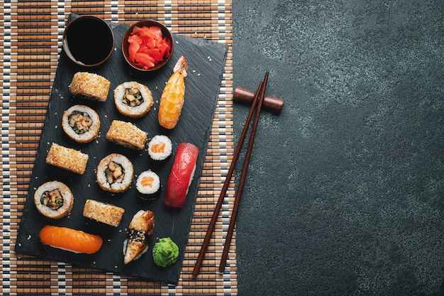Set of sushi and maki on dark stone table. top view with copy space. flat lay.