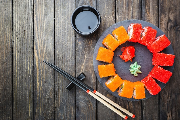 Set of sushi or maki roll on stone plate over black wooden table