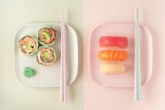 Set of sushi, maki and rolls on colored plates with chopsticks